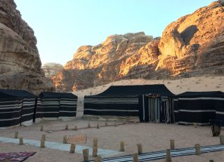 Die Sonne geht über dem Wadi Rum unter, wir haben das Zeltlager erreicht